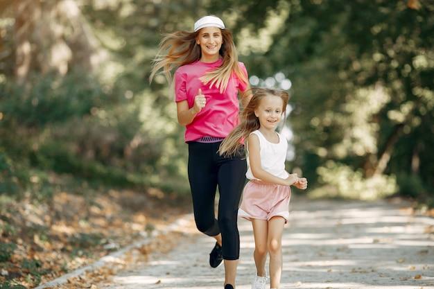 Mãe com filha fazendo esporte em um parque de verão
