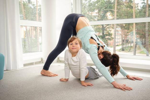 Mãe com filha fazendo exercícios de ioga