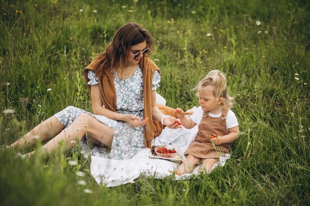 Mãe com filha fazendo piquenique no parque