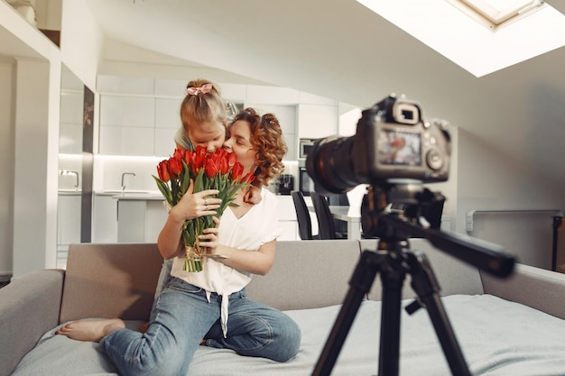 Mãe com filha filma um blog em casa