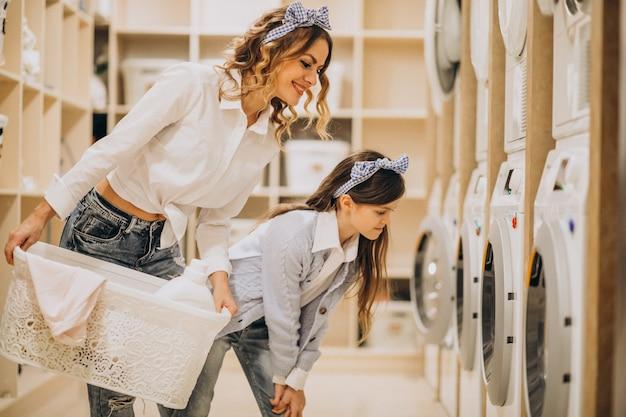 Mãe com filha lavando roupa na lavanderia self-service