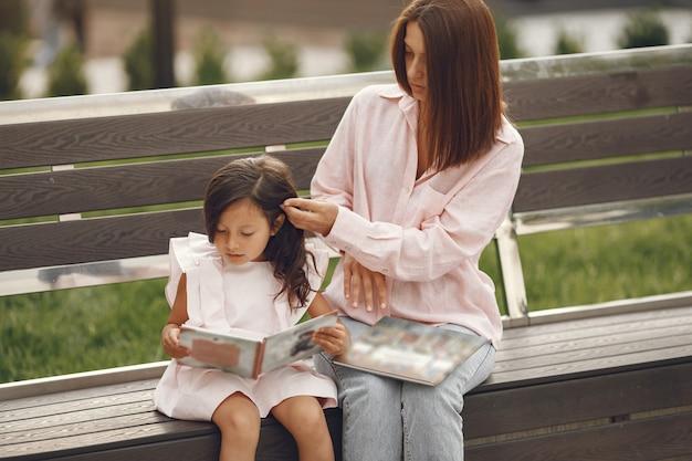 Mãe com filha lendo um livro na cidade