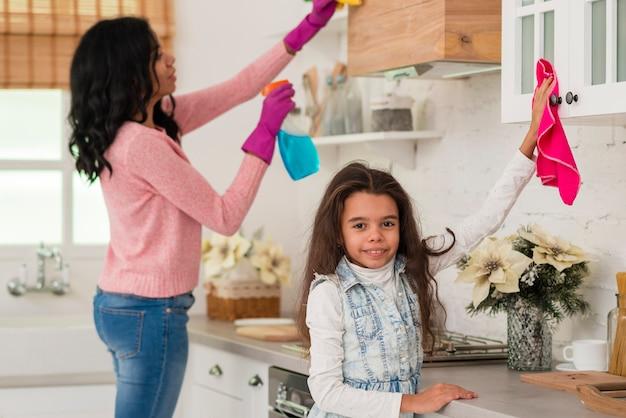 Mãe com filha limpando a casa