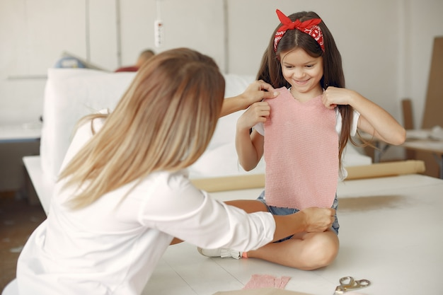 Mãe com filha medir o tecido para costura
