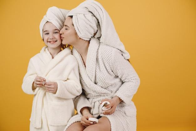 Mãe com filha. meninas com roupões de banho brancos. mãe ensina filha a fazer maquiagem.