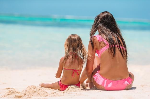 Mãe com filha na praia.