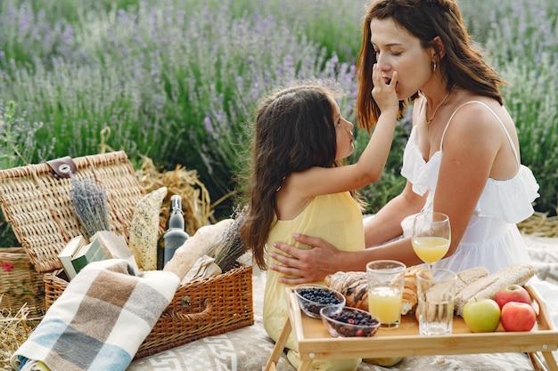 Mãe com filha no campo de lavanda. mulher bonita e bebê fofo brincando no campo do prado. família em um piquenique.