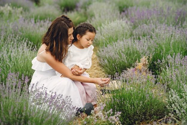 Mãe com filha no campo de lavanda. mulher bonita e bebê fofo brincando no campo do prado. férias em família num dia de verão.