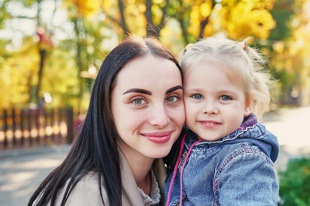 Mãe com filha no parque outono