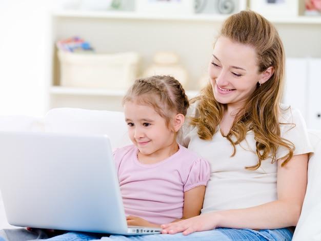 Mãe com filha olhando para laptop
