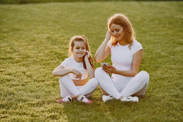 Mãe com filha ouvindo música em um parque
