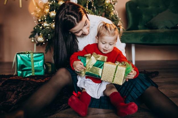 Mãe com filha pela árvore de natal