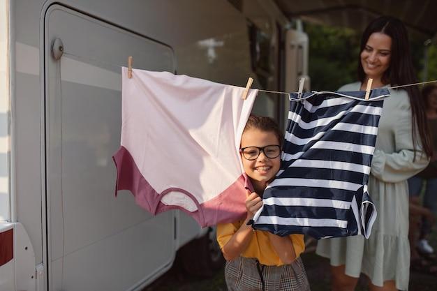 Mãe com filha pendurando roupas de carro ao ar livre no acampamento, viagem de férias em família de caravana.