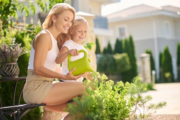 Mãe com filha pequena regando flores perto de casa