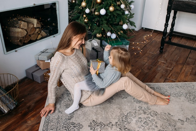 Mãe com filha perto de árvore de natal em casa