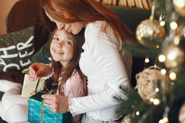 Mãe com filha perto de árvore de natal