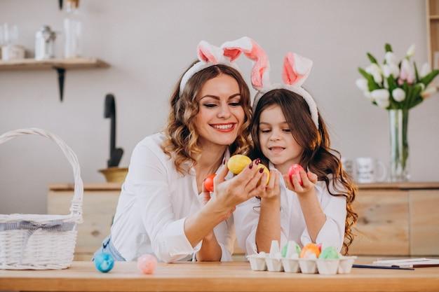 Mãe com filha pintando ovos para a páscoa