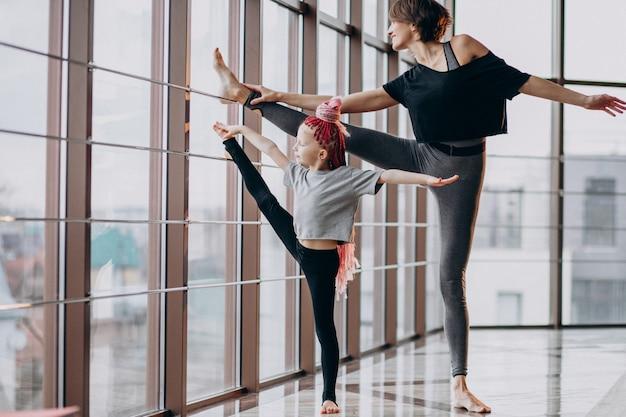Mãe com filha praticando ioga pela janela