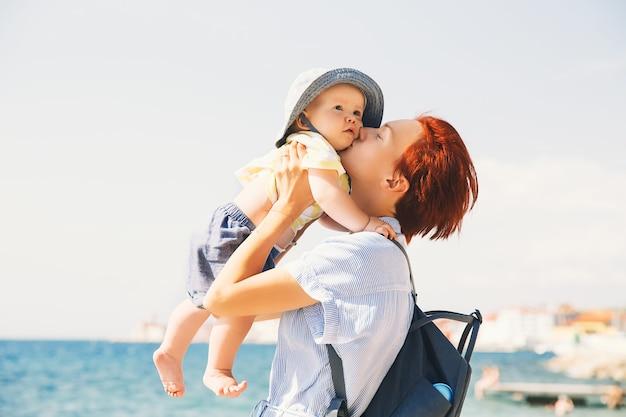 Mãe com filha se divertindo na costa perto da praia do mar mulher e bebê de férias na europa