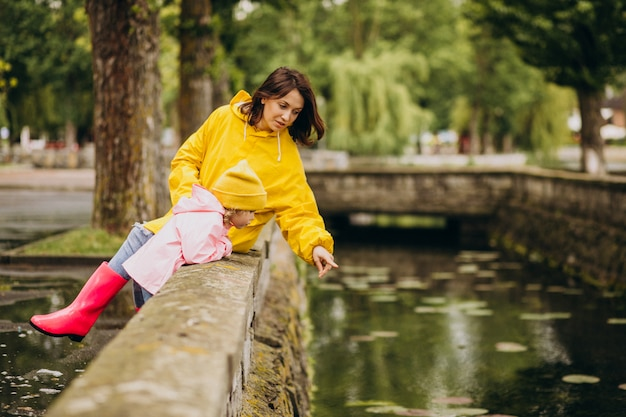 Mãe com filha se divertindo no parque em um tempo chuvoso