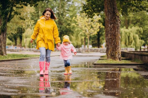Mãe com filha se divertindo pulando nas poças