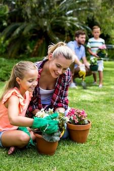 Mãe com filha segurando vasos de flores no quintal