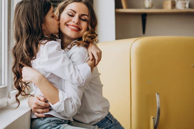 Mãe com filha sentada na cozinha