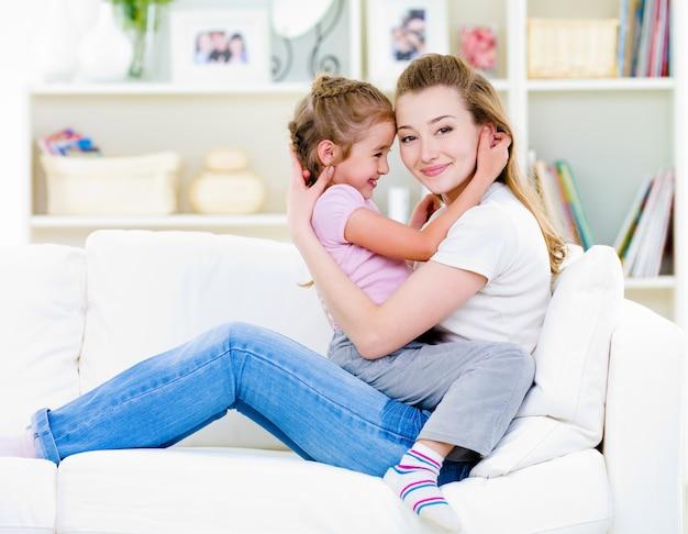 Mãe com filha sentada no sofá