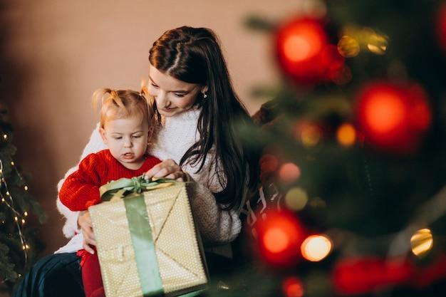 Mãe com filha sentada perto da árvore de natal