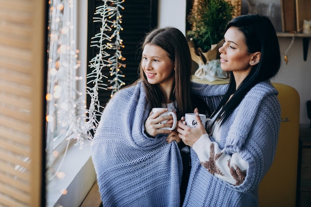 Mãe com filha tomando chá juntos na cozinha perto da janela