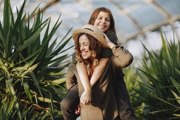 Mãe com filha. trabalhadores com potes de flores. menina em uma camisa verde