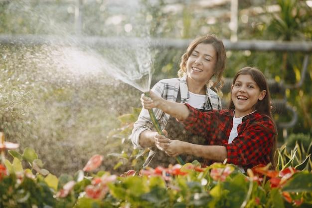 Mãe com filha. trabalhadores com potes de flores. pessoas derramam flores