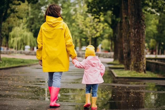 Mãe com filha vestindo capa de chuva e botas de borracha, andando em um tempo chuvoso