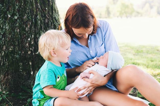 Mãe com filhinha e filho mais velho caminhando ao ar livre cuidados e amamentação do bebê