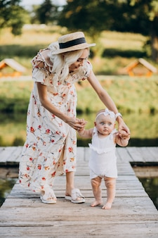 Mãe com filhinha perto do lago