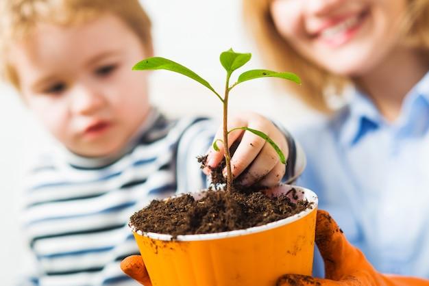 Mãe com filho a plantar flores. relações familiares. descoberta e ensino de jardinagem.