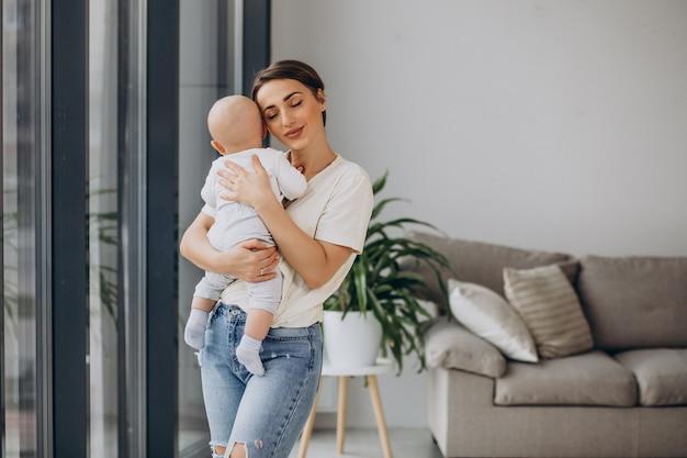 Mãe com filho bebê em casa perto da janela