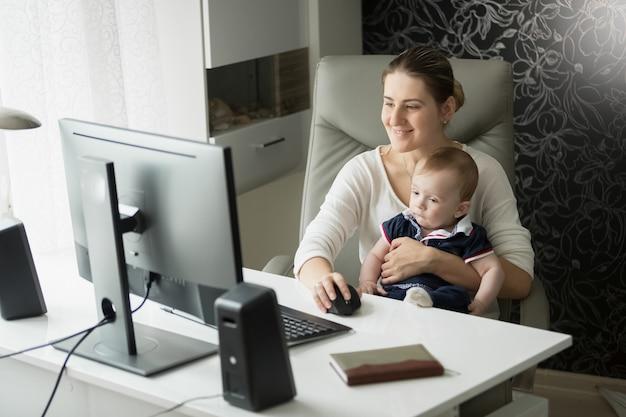 Mãe com filho bebê no escritório usando computador