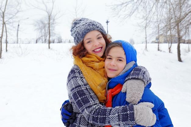 Mãe com filho brincando no parque de inverno