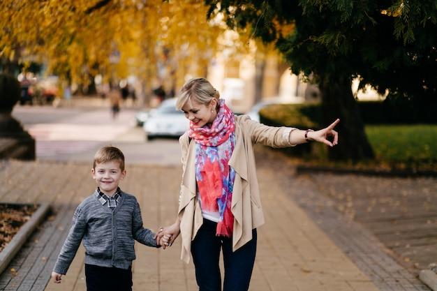 Mãe com filho caminhando ao ar livre no outono
