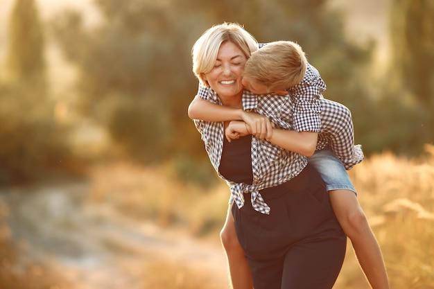 Mãe com filho caminhando em um campo de primavera