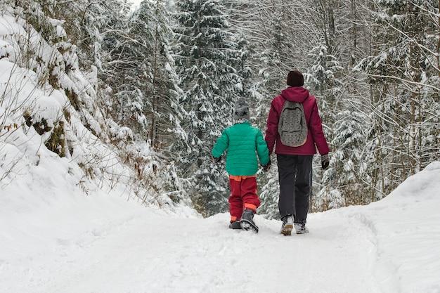 Mãe com filho caminhando pela estrada coberta de neve