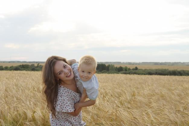 Mãe com filho caminhando por um campo de trigo