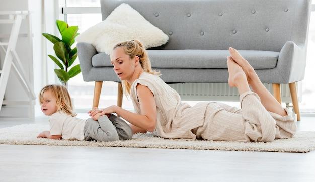 Mãe com filho deitado no chão fazendo exercícios de ioga juntos em casa