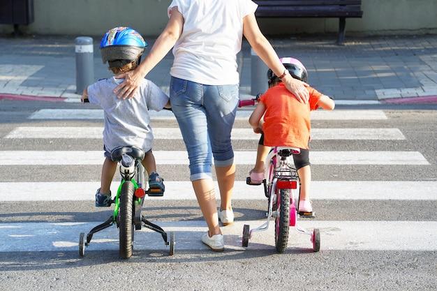 Mãe com filho e filha com uma bicicleta em uma zebra