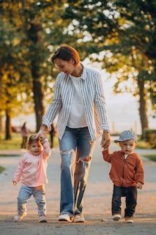 Mãe com filho e filha pequenos no parque outonal