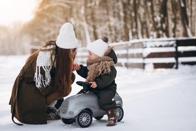 Mãe com filho em um carro pequeno no inverno