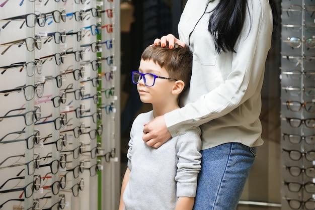 Mãe com filho escolhendo óculos na loja de ótica.