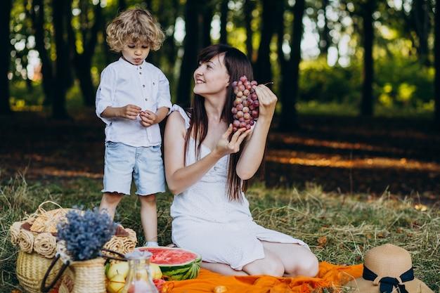 Mãe com filho fazendo piquenique na floresta