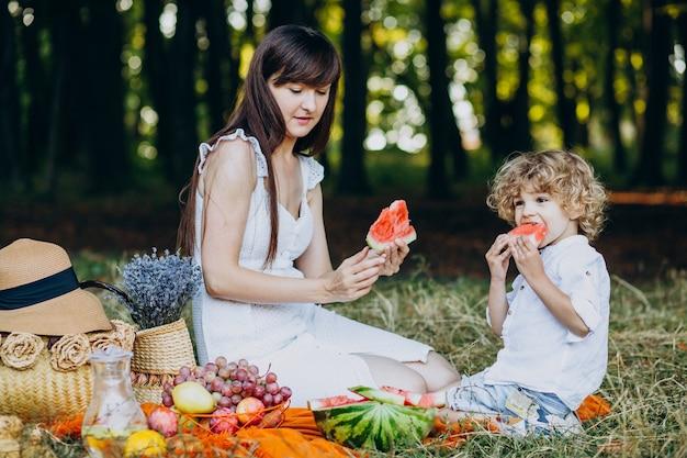 Mãe com filho fazendo piquenique no parque